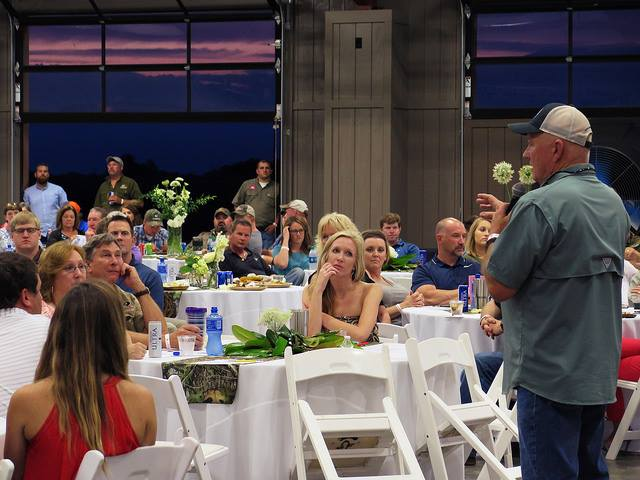 speaker at auction dinner event during Mossy Oak Properties Charity Event