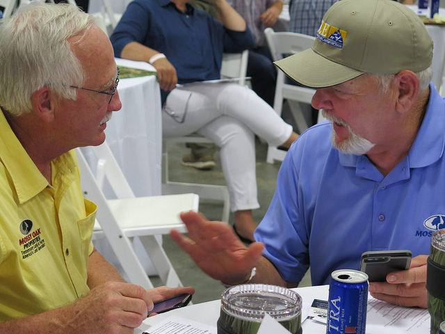 two men at auction dinner during Mossy Oak Properties Charity Event